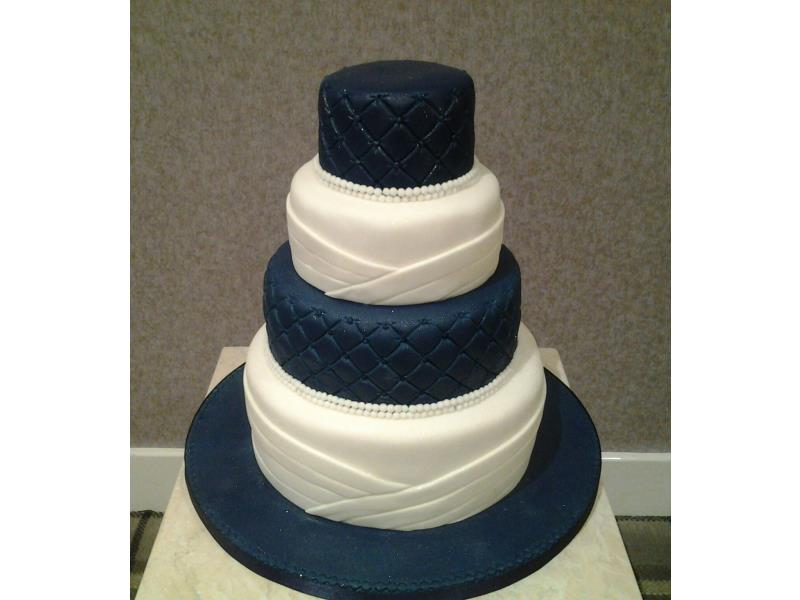 Simplistic royal blue and white 4 tier wedding cake with pearls. Made in vaniila and chocolate with orange sponges and carrot cake.