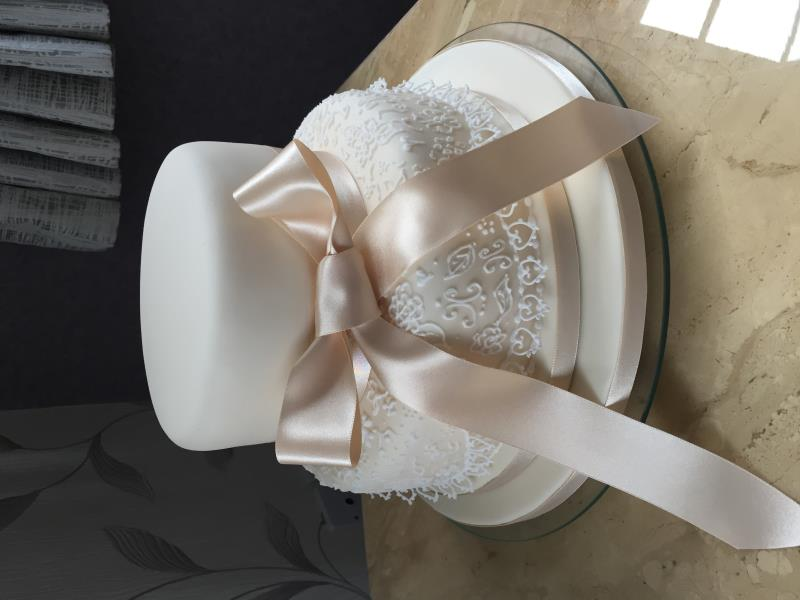 Champage aand white 2 tier wedding cake in vanilla sponge.One plain tier and piped emboidery on the other.