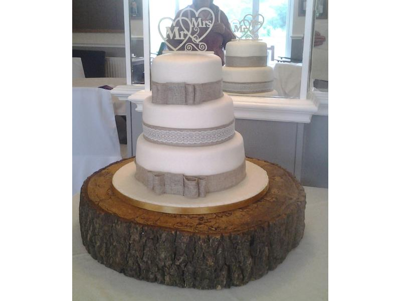 3 tier Hessian wedding cake on rustic log. Plain and classic in design with clients choice of topper. Made from vanilla, chocolate and lemon sponges.