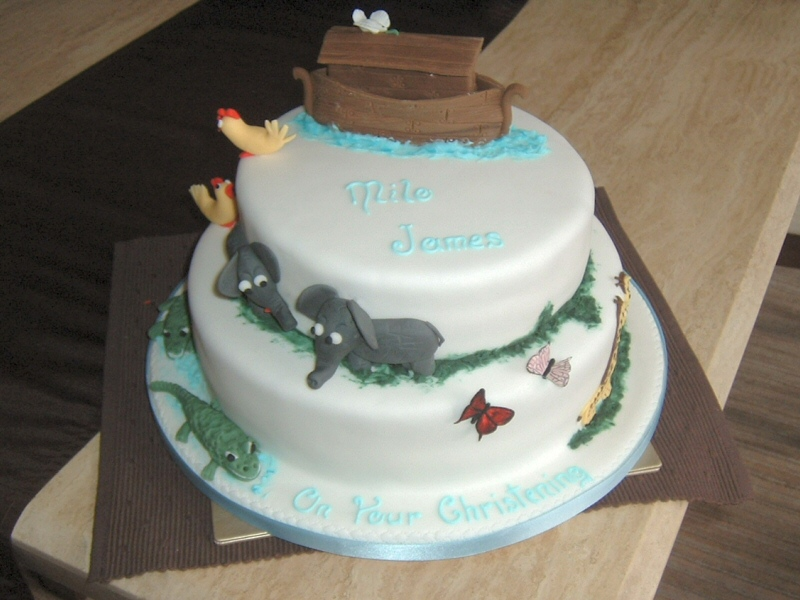 Milo - 2 tier stacked christening cake with hand modelled suger animal decoration depicting the Ark and animals arriving two by two