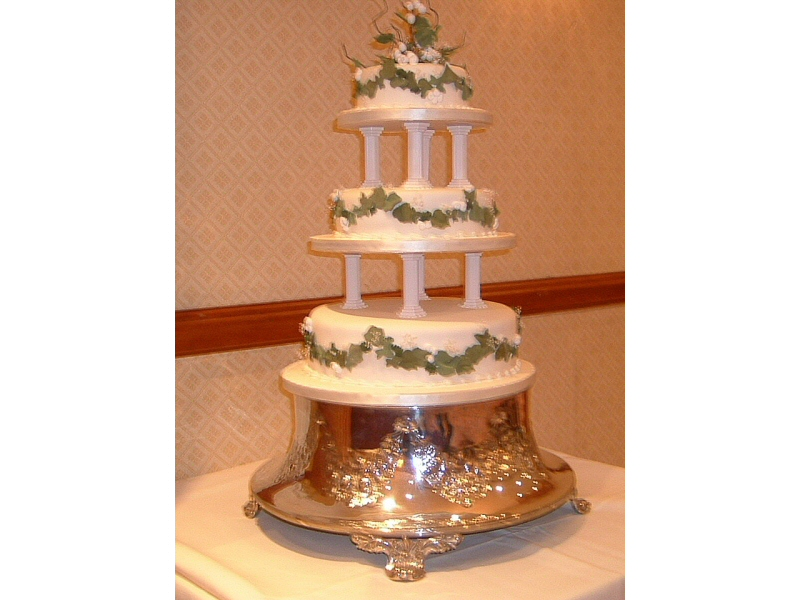 Julie - 3 tier cream pillared wedding cake with garlands of ivy leaves and berries