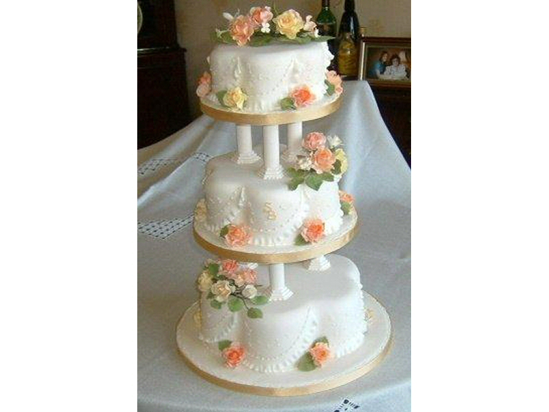 Sandra - 3 tier cream petal shaped cake with roses frilling, together with monograms of the bride and groom